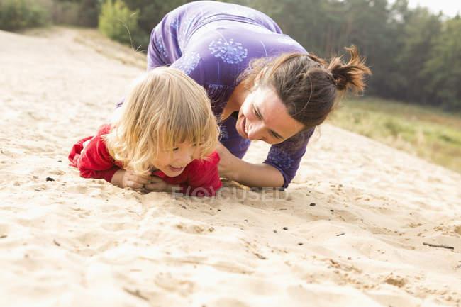Счастливая мать играет с дочерью на песке — стоковое фото