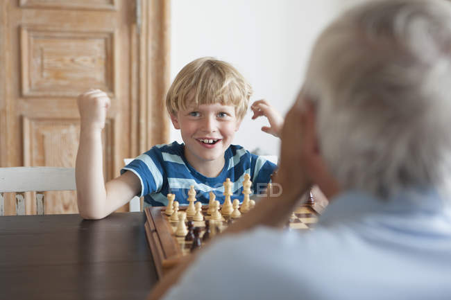 Happy grandson playing chess with grandfather at home — Stock Photo