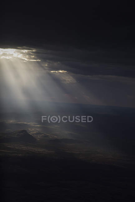 Sun streaming through storm clouds on arid landscape — Stock Photo