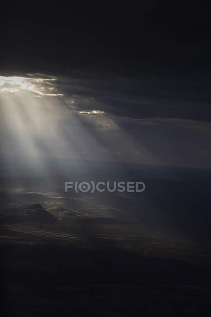 Sole in streaming attraverso le nubi di tempesta il paesaggio arido — Foto stock