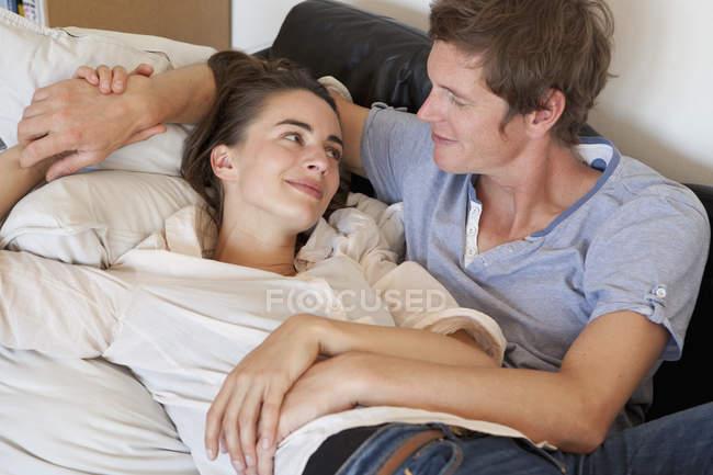 Feliz pareja joven descansando en el sofá - foto de stock
