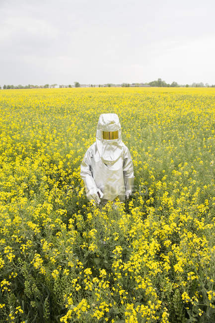 Person in a radiation protective suit walking in oilseed rape field — Stock Photo