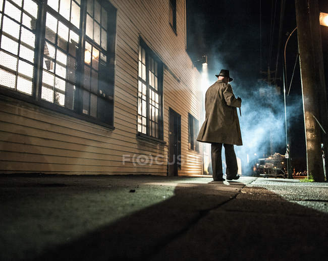 Rear view of man walking outside industrial building at night — Stock Photo