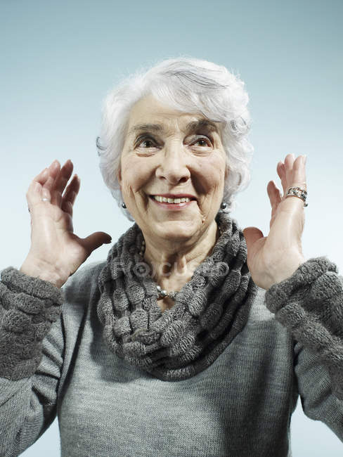 Portrait of senior woman with arms raised in surprise — Stock Photo