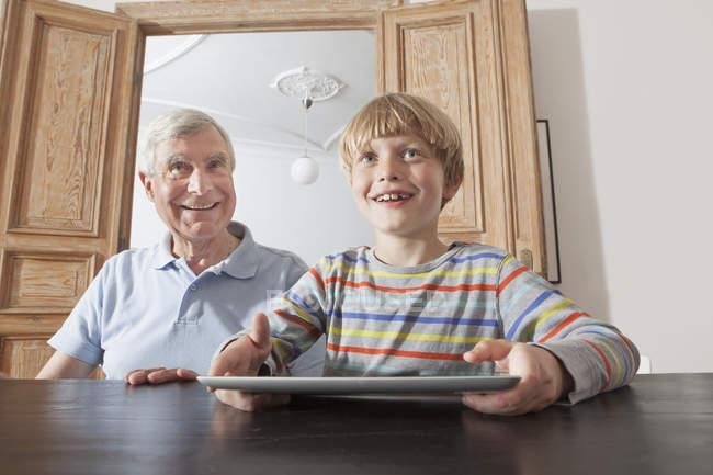 Heureux homme âgé assis avec petit-fils tenant tablette numérique à la maison — Photo de stock