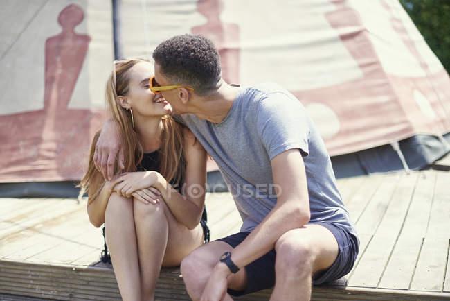 Молодая пара целуется на вигваме во время гламура — стоковое фото
