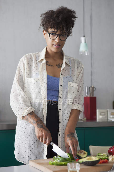 Portrait of young woman cutting vegetables in kitchen — Stock Photo