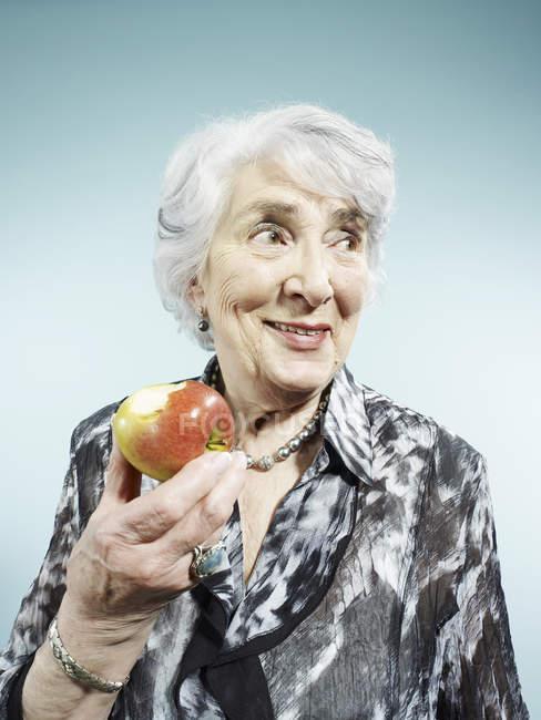 Seniorin hält Apfel auf blauem Hintergrund — Stockfoto