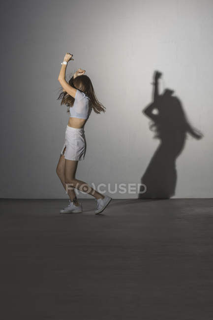 Full length of woman dancing against gray wall with shadow — Stock Photo