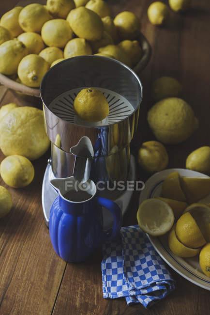 Blauer Krug und elektrische Saftpresse von Zitronen auf Holztisch — Stockfoto