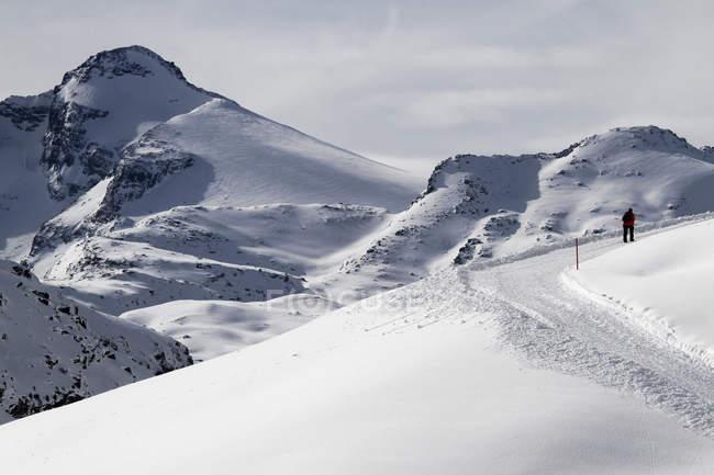 Escursionista solitario che sale sulla collina di neve — Foto stock