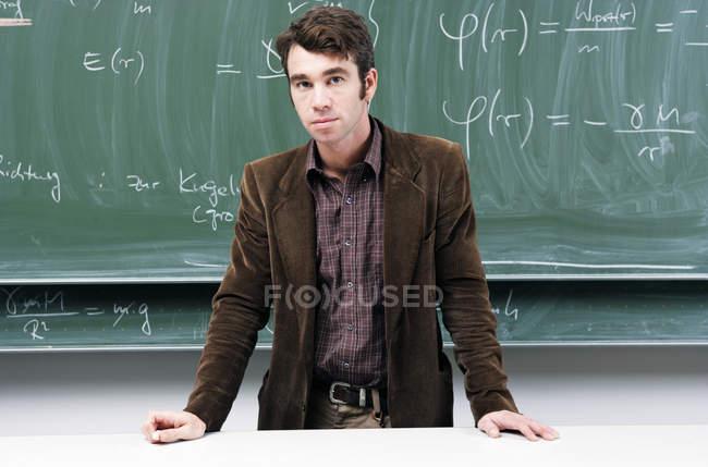 Maestro de pie delante de la pizarra con ecuaciones de física - foto de stock