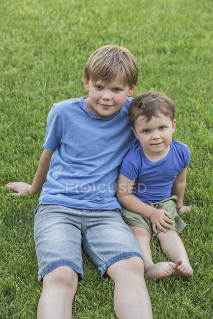 Portrait of brothers relaxing in park — Stock Photo