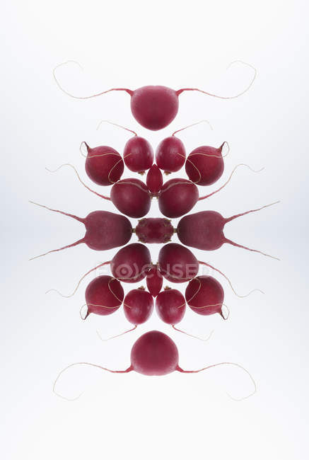 Composite of mirrored radishes on white backdrop — Stock Photo