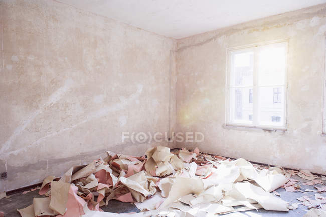 Interior view of messy room with pile of teared wall papers on floor — Stock Photo