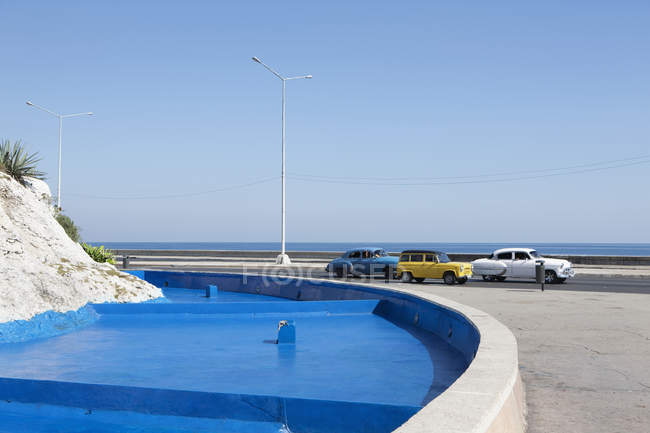 Classic cars moving by blue fountain against clear sky — Stock Photo
