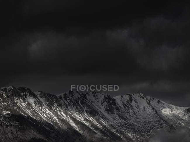Cielo oscuro con un po 'di luce solare che irrompe oltre la catena montuosa — Foto stock