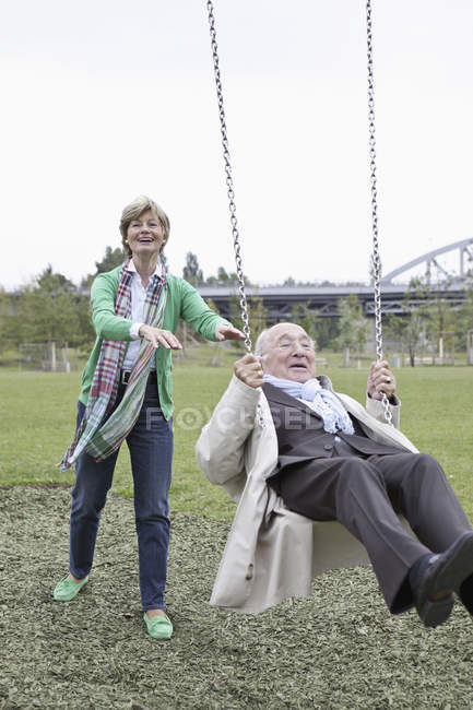 Cheerful senior couple playing on park swing — Stock Photo