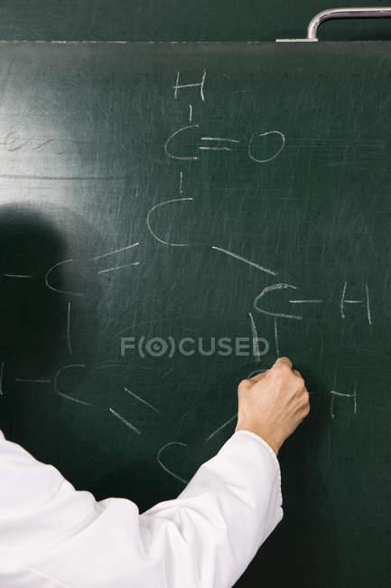Un professeur de chimie écrit une formule sur un tableau, se concentre sur la main — Photo de stock