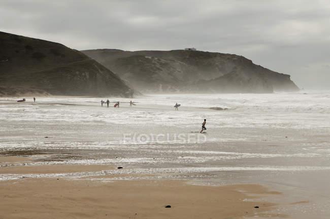 Vista distante de pessoas na praia contra falésias costeiras — Fotografia de Stock