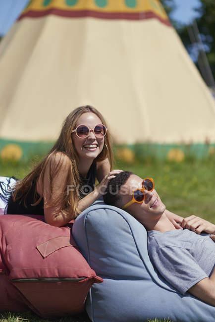 Casal feliz mentindo em travesseiros enquanto glamping no verão — Fotografia de Stock