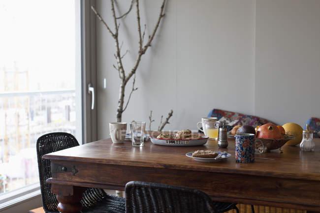 Сніданок на дерев'яні обідній стіл, за вікном — стокове фото