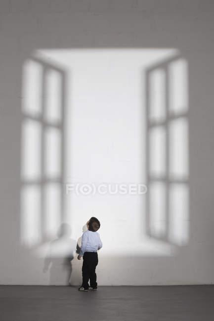 Мальчик смотрит на тень открытого окна на белой стене — стоковое фото