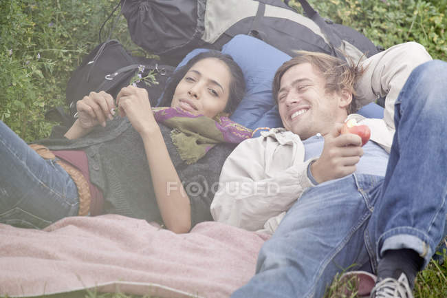 Young couple relaxing on backpacks in field — Stock Photo