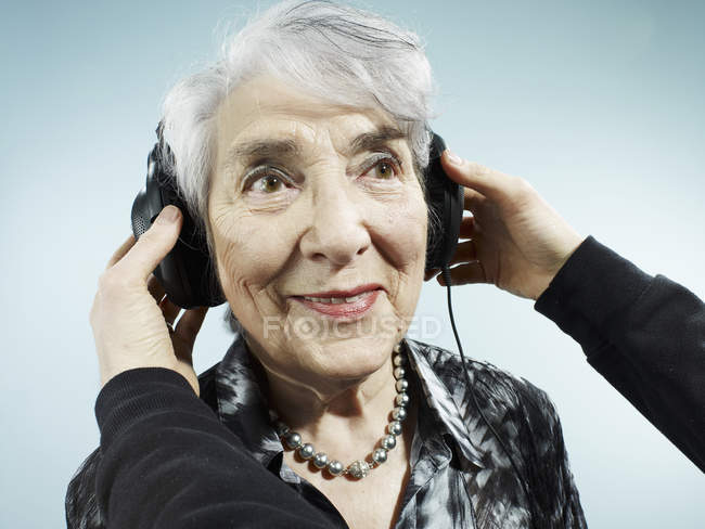 Person putting on headphones on senior woman on blue background — Stock Photo