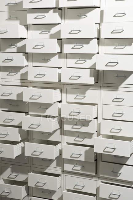 Armário branco com gavetas abertas em graus variados — Fotografia de Stock