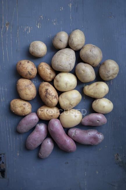 Verschiedenen Kartoffeln auf Holztisch — Stockfoto