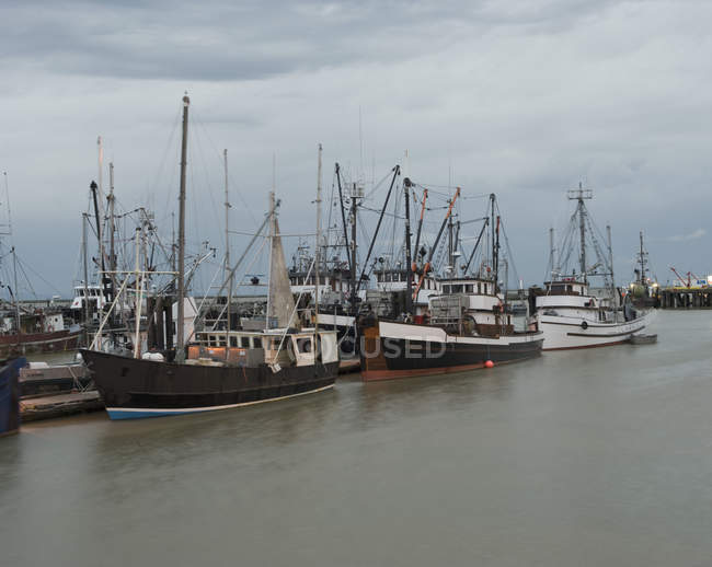 Fishing fleets at docks on cloudy day — Stock Photo