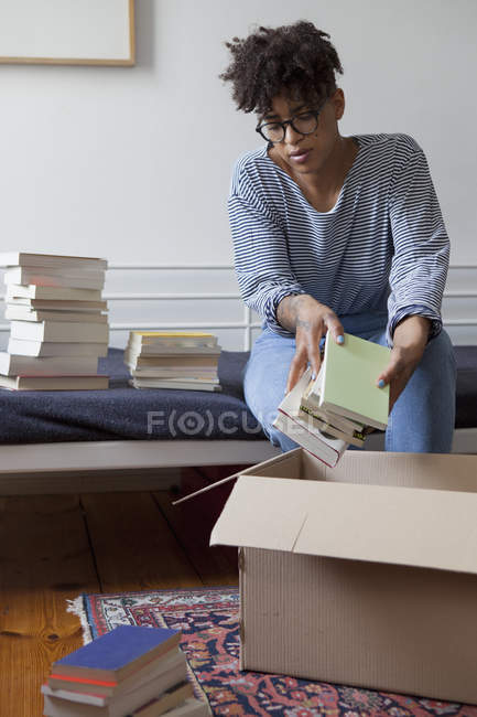 Young woman packing books in cardboard box at home — Stock Photo
