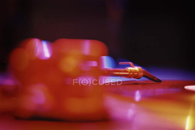 Close up view of vinyl record playing on turntable in red light — Stock Photo
