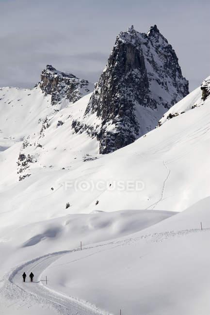 Vista de los caminantes hacen su camino a lo largo de la ruta de la nieve - foto de stock