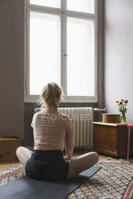 Rückansicht der Frau beim Yoga im Wohnzimmer — Stockfoto