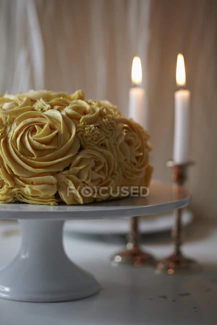 Stillleben mit Rosen Kuchen und Kerzen auf den Tisch — Stockfoto