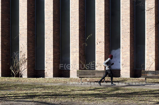 Man jogging along sidewalk in city during springtime — Stock Photo