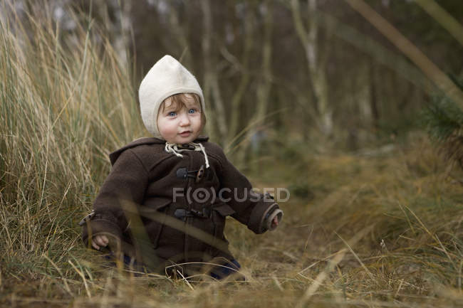 Baby girl in warm clothing sitting in grass — Stock Photo