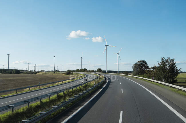 Wind turbines along empty highway on sunny day — Stock Photo