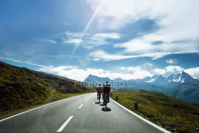 Rear view of cyclists moving on scenic mountain road — Stock Photo