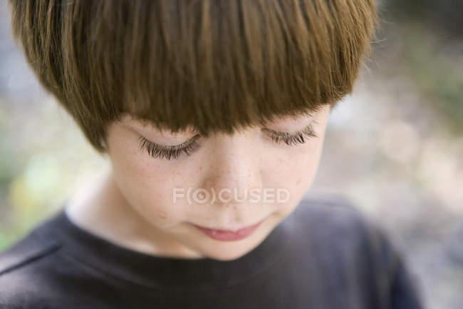 Портрет мальчика, смотрящего вниз — стоковое фото