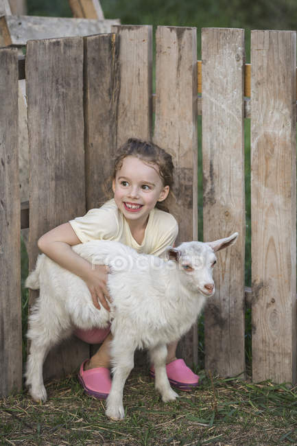 Young girl holding baby goat — Stock Photo