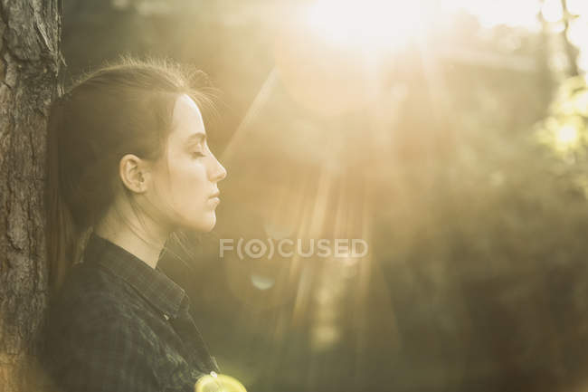 Side view of young woman with eyes closed enjoying sunlight at park — Stock Photo