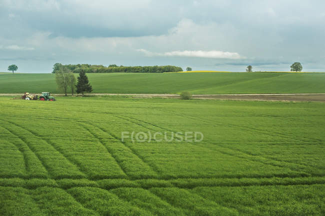 Tranquil scene of agricultural landscape with traktor working in field — Stock Photo