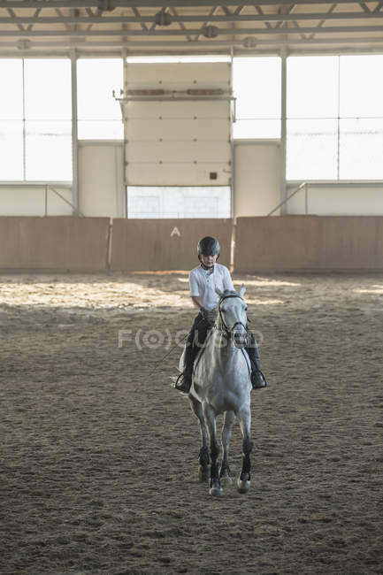 Menino cavalgando cavalo no estábulo de treinamento — Fotografia de Stock