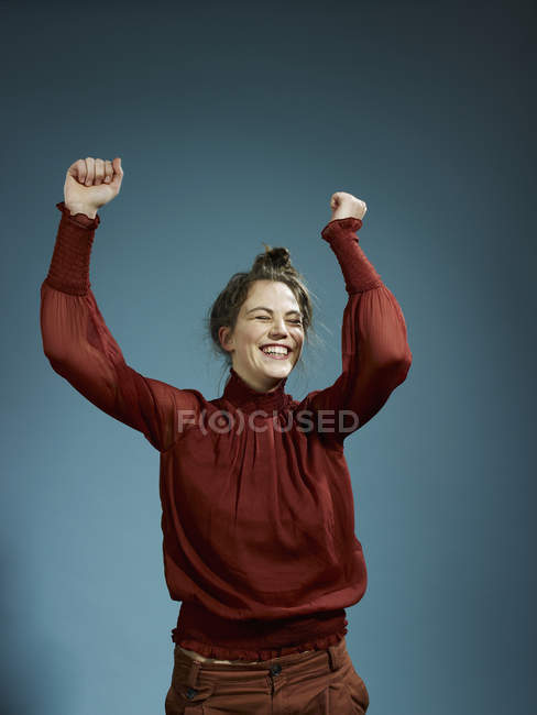 Young woman with arms raised in celebration on blue background — Stock Photo