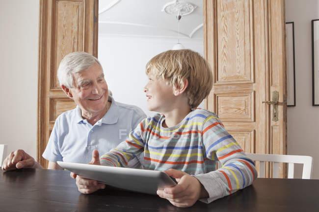 Heureux homme âgé regardant petit-fils avec tablette numérique à la maison — Photo de stock