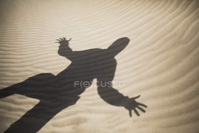 Rippled sand with shadow of man with arms outstretched — Stock Photo