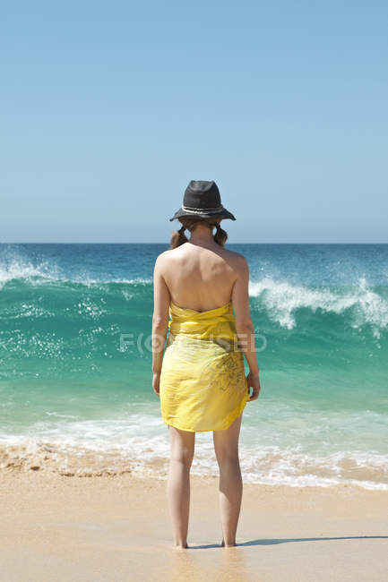 Rear view of woman standing ankle deep in sand at beach — Stock Photo